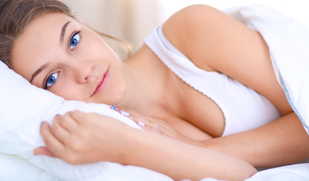 blissfully: A beautiful young woman lying in bed comfortably and blissfully.
