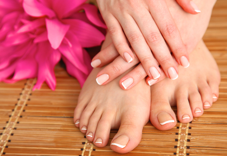 manicure salon: Care for beautiful woman legs with flower .