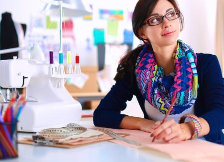 dressmaker: Dressmaker designing clothes pattern on paper
