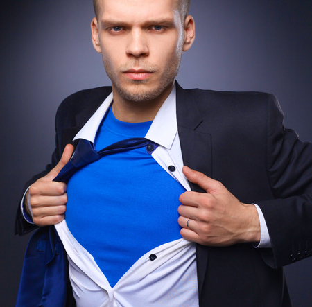 tearing: Young businessman acting like a super hero and tearing his shirt, isolated on gray background . Stock Photo