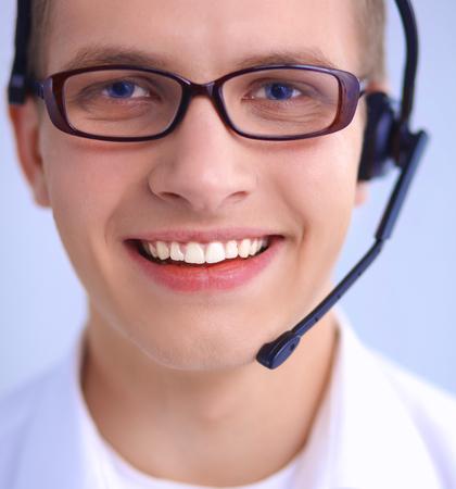 handsfree telephone: Call center male operator on gray background
