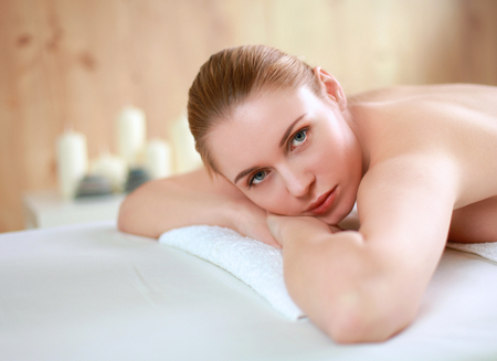 holistic care: Young woman getting spa massage, lying on spa salon Stock Photo