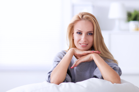 woman couch: Young beautiful woman sitting on couch at her room .