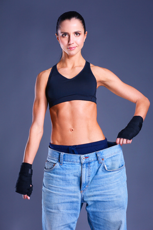 wondered: Young fitness woman showing that her old jeans .