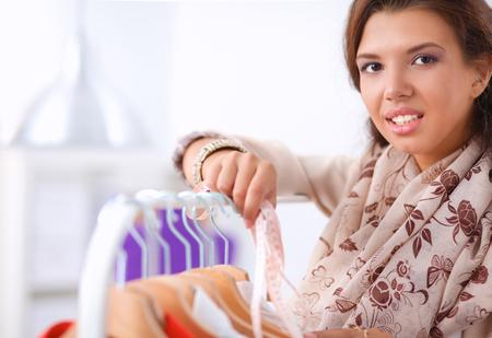 estilista: Estilista joven hermosa cerca de estante con perchas
