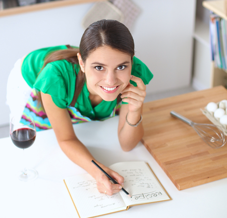 noting: Happy beautiful woman standing in her kitchen writing on a notebook