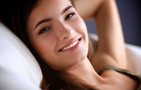 home comforts: Closeup of a smiling young woman lying on couch.