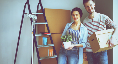 property ladder: Happy young couple unpacking or packing boxes and moving into a new home.