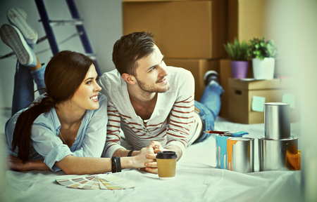 paint swatch: Couple choosing paint colour from swatch for new home lying on wooden floor. Stock Photo