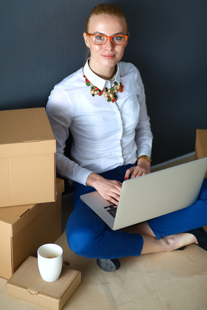 to unpack: Woman sitting on the floor near a boxes  with laptop .