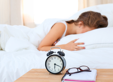 timepiece: A young woman putting her alarm clock off in the morning.