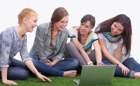 mujer mirando el horizonte: Grupo de tres chicas adolescentes que ríen mientras observa el ordenador portátil sentado en la hierba. Foto de archivo