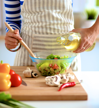 the mixing: Young woman mixing fresh salad . Stock Photo