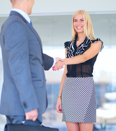 business relationship: Businesswoman Shaking Hands In Office Stock Photo