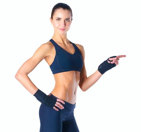 mujer deportista: mujer joven muscular que presenta en ropa deportiva contra el fondo blanco. Foto de archivo