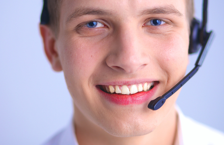 handsfree telephone: Call center male operator on gray background