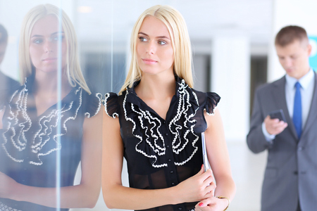 ambitious: Business woman standing in foreground in office .