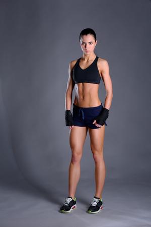 mujer deportista: mujer joven muscular que presenta en ropa deportiva contra el fondo negro.