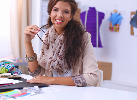 Smiling female fashion designer sitting at office desk, isolated