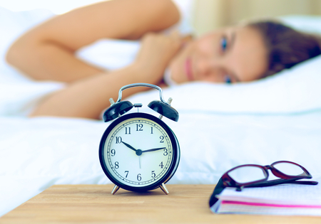 awaking: A young woman putting her alarm clock off in the morning.