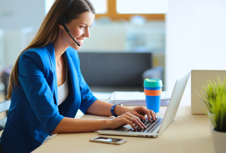 Portrait de la belle femme d'affaires travaillant à son bureau avec un casque et un ordinateur portable. Banque d'images - 60872216