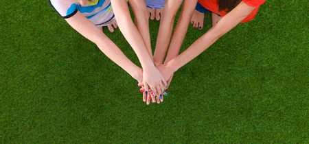 unanimous: People joining their hands standing on green grass. Stock Photo