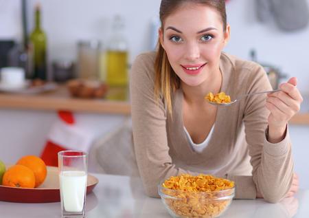 comiendo cereal: Mujer sonriente que desayuna en el interior de la cocina