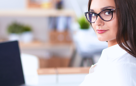 Attractive businesswoman sitting  in the office, at the desk Stock Photo