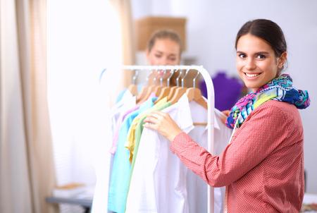 estilista: Beautiful young stylist near rack with hangers