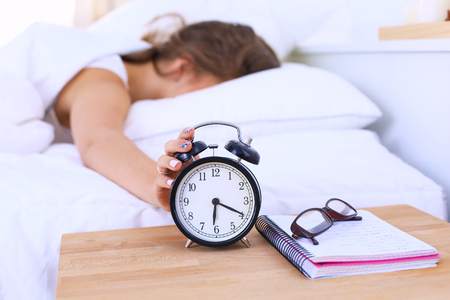 tired person: A young woman putting her alarm clock off in the morning.