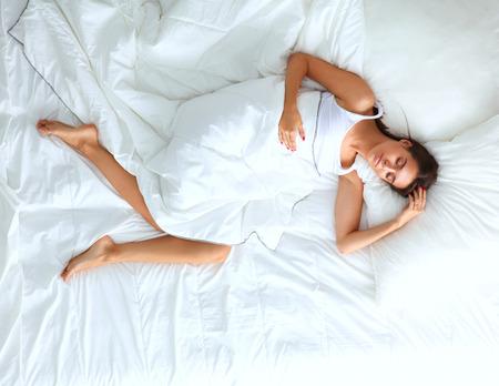 Giovane bella donna sdraiata a letto.