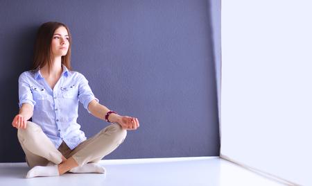 Joven mujer sentada en el suelo cerca de la pared oscura.