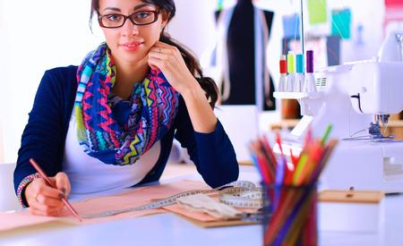 dressmaker: Dressmaker designing clothes pattern on paper .