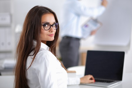 principal: Attractive businesswoman sitting in the office, at the desk
