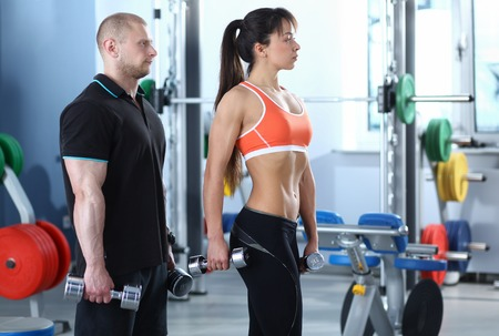 healthy men: Beautiful woman at the gym exercising with her trainer . Stock Photo