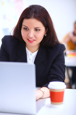 Attractive businesswoman sitting in the office, at the deskwith cup of coffee.