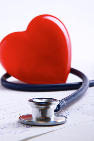 Red heart and a stethoscope isolated on white background. Stock Photo