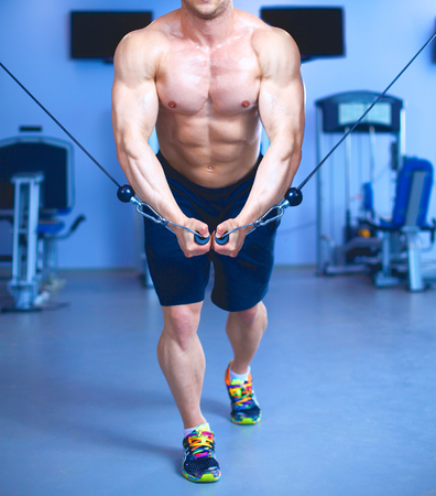 Entrenamiento del hombre joven en el gimnasio con ejercicios.