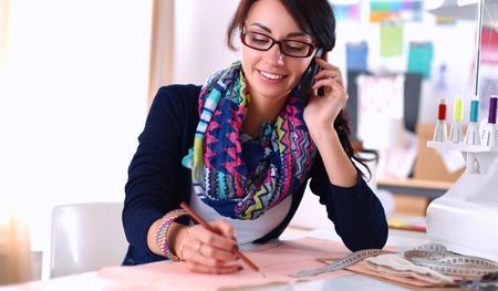 dressmaker: Dressmaker woman designing clothes pattern on paper .