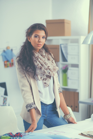 Smiling female fashion designer sitting at office desk . Stock Photo