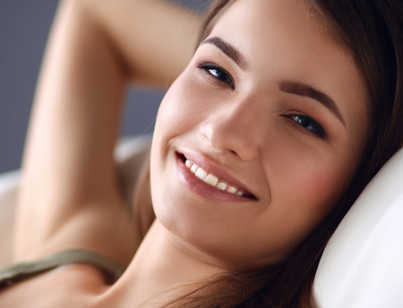 woman on couch: Closeup of a smiling young woman lying on couch Stock Photo