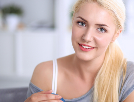 woman on couch: Young beautiful woman sitting on couch at her room