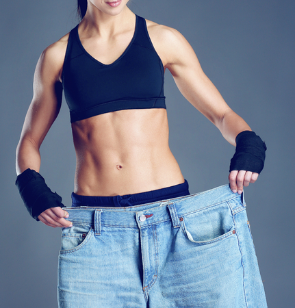 waistline: Young fitness woman showing that her old jeans