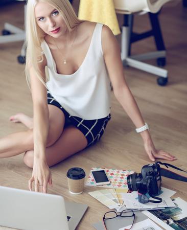Fashion designers working in studio sitting on the floor Stock Photo