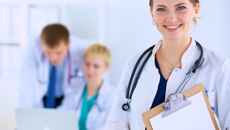 Attractive female doctor with folder in front of medical group .