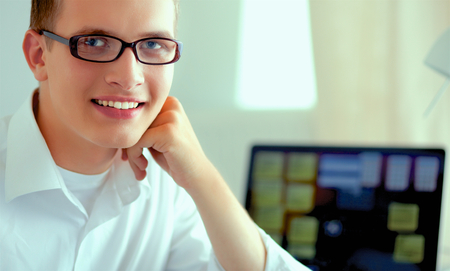 Young businessman working in office, sitting at desk Stock Photo
