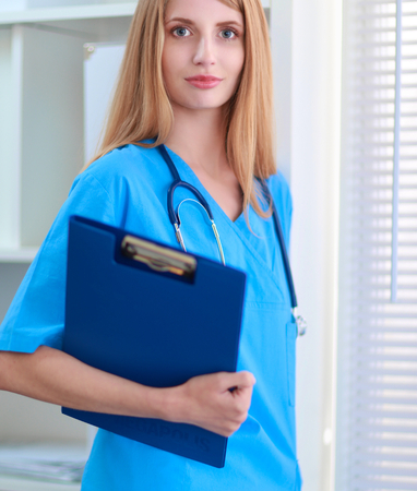 smock: Portrait of woman doctor with folder at hospital corridor