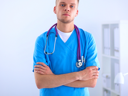 Doctor with stethoscope standing , crossed arms, isolated on white background