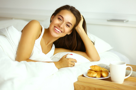 Beautiful young woman sitting in bed and having breakfast Stock Photo