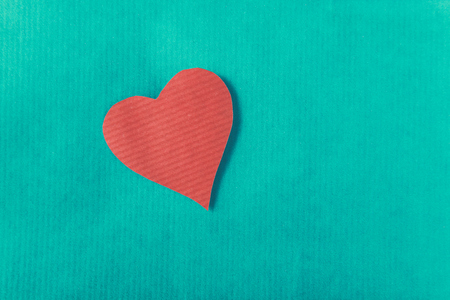 Red heart with ribbon, isolated on green background.